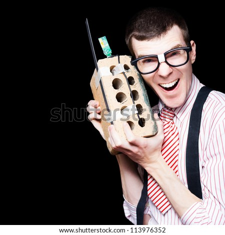 Laughing Business Geek Talking On A Mobile House Brick Telephone In A Funny Depiction Of The Wireless Technology Evolution - stock photo