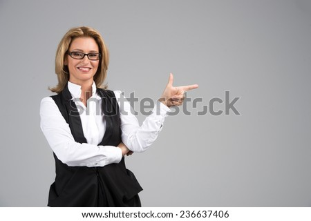 Laughing business woman in white shirt. Attractive mature businesswoman on white background pointing with finger - stock photo