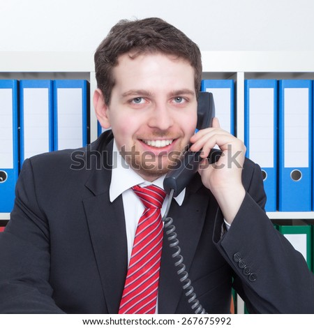 Laughing businessman in a black suit at office at phone - stock photo