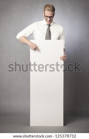 Laughing businessman looking and  pointing finger at white blank vertical billboard with space for text isolated on grey background. - stock photo