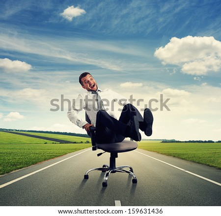 laughing businessman sitting on the office chair and rolling on the road - stock photo