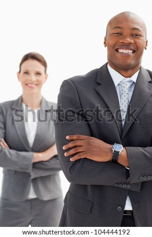 Laughing businessman stands in front of businesswoman - stock photo