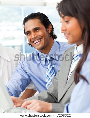 Laughing businessman working with his team in the office - stock photo