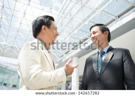 Laughing businessmen standing and talking inside