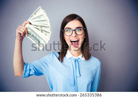Laughing businesswoman holding bills of dollar over gray background. Wearing in blue shirt and glasses. Looking at camera  - stock photo