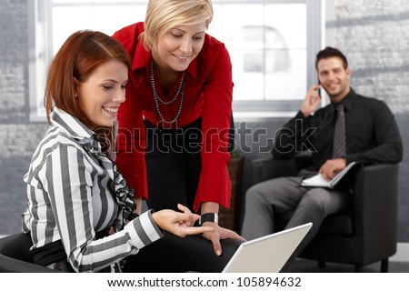 Laughing businesswomen using laptop computer in office lobby businessman in background. - stock photo