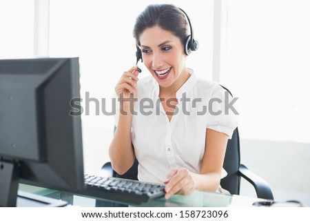 Laughing call center agent sitting at her desk on a call in her office - stock photo