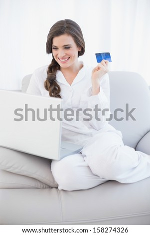 Laughing casual brown haired woman in white pajamas shopping online with her laptop in a bright living room - stock photo