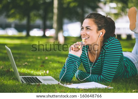 Laughing casual student lying on grass taking notes on campus at college - stock photo
