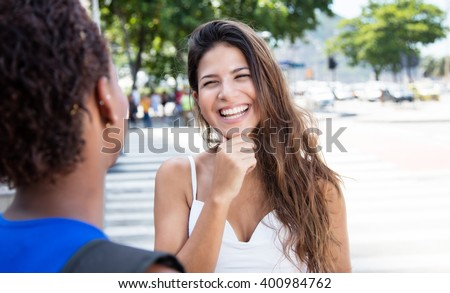 Laughing caucasian girl speaking with african american girlfriend - stock photo
