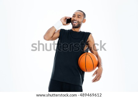 Laughing cheerful african basketball player talking on mobile phone isolated on a white background