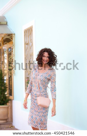 laughing cheerful middle aged brunette with a handbag near the white wall of an old building. woman in a summer dress for a walk - stock photo