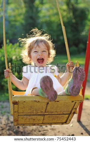 Laughing child on swing in summer park - stock photo