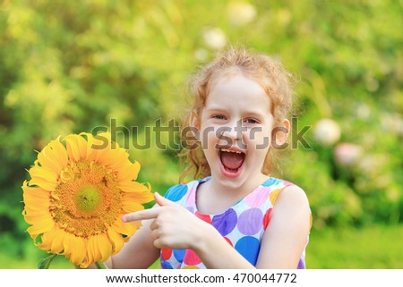 Laughing child with holds sunflower. Healthcare, medical and happy childhood concept.