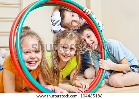 Laughing children holding hula hoops in a school gym - stock photo