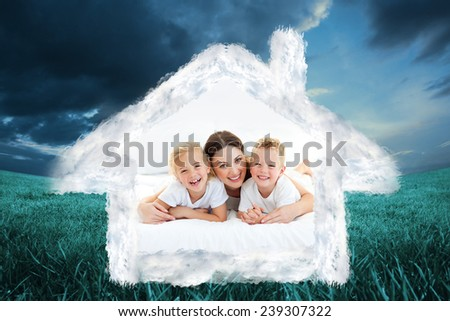 Laughing children playing with their mother lying on a bed against blue sky over green field - stock photo