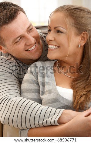 Laughing couple looking at each other hugging, smiling. - stock photo