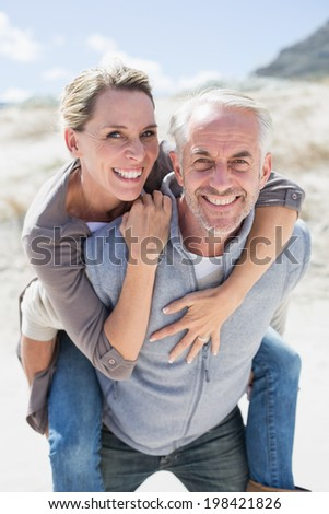 Laughing couple smiling at camera on the beach on a bright but cool day - stock photo