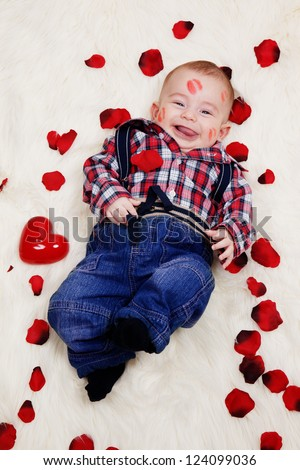 Laughing cute boy with lipstick on his face lying with rose petals. - stock photo