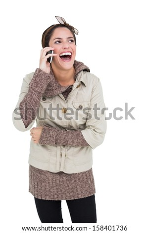 Laughing cute brunette in winter fashion phoning on white background - stock photo