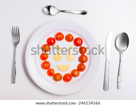 laughing emoticon food, made from cheese and tomatoes, on a plate with cutlery, isolated