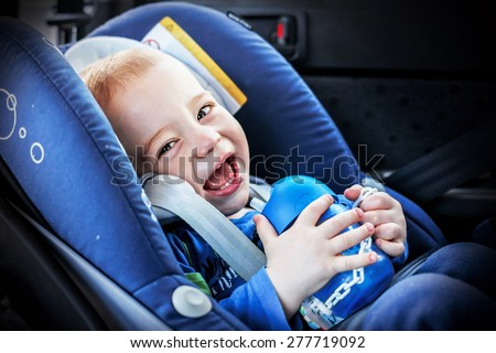 Laughing fair hair little boy in the child car safety seat with his pot. Image with toning and selective focus - stock photo