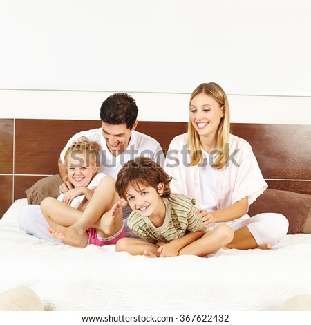 Laughing family having fun with children on bed in a bedroom - stock photo