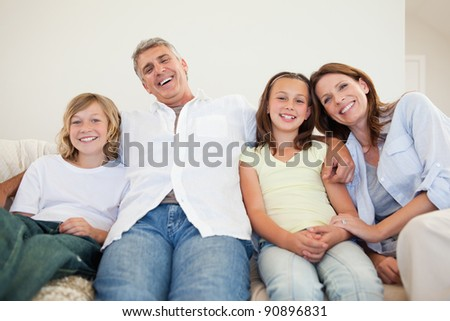 Laughing family sitting on the couch together