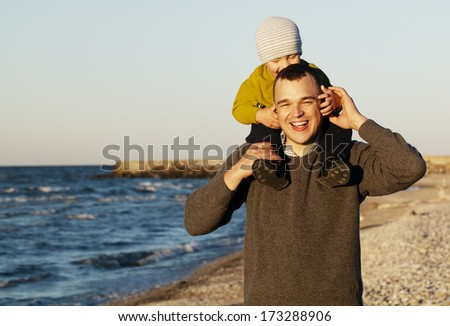 Laughing father giving a toddler a piggy back ride as they take a refreshing walk along a beach in evening sunshine - stock photo