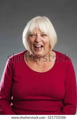 Laughing - female senior portrait series on grey background. - stock photo