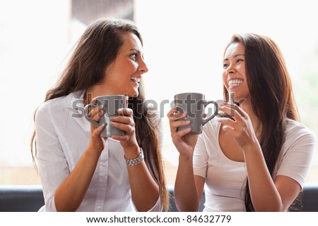 Laughing friends having a coffee in a cafe - stock photo