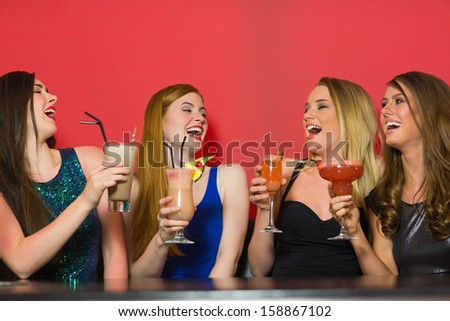 Laughing friends holding cocktails and chatting in a nightclub - stock photo
