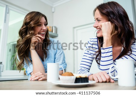 Laughing friends holding coffee mugs at table in kitchen - stock photo