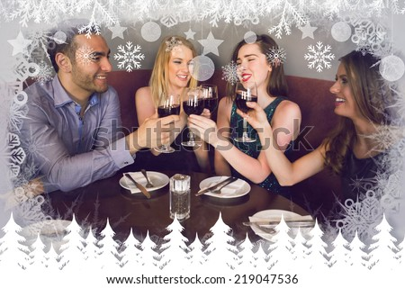 Laughing friends sitting together clinking glasses against fir tree forest and snowflakes - stock photo