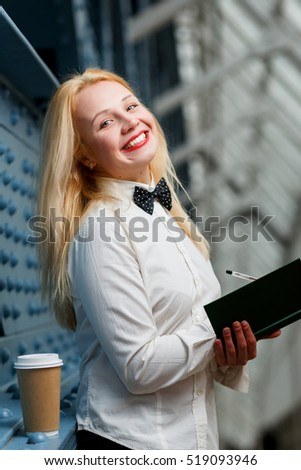 Laughing ginger woman in white shirt holding note-book