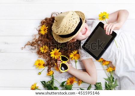 Laughing girl in a straw hat resting on the tablet in her hands. Dreaming of a rustic holiday. - stock photo