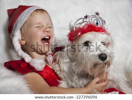 laughing girl in Santa's cap with white dog