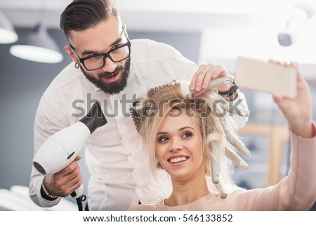 Laughing girl is taking picture with a stylist
