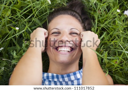 laughing girl lying on a lawn - stock photo