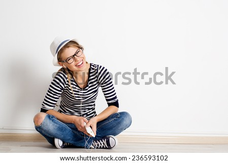 Laughing girl sitting on wooden flooring with smart phone in headset. Music, leisure and technology concept.  - stock photo
