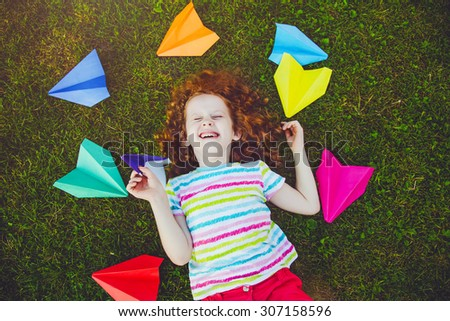 Laughing girl throwing paper airplane in green grass at summer park. - stock photo