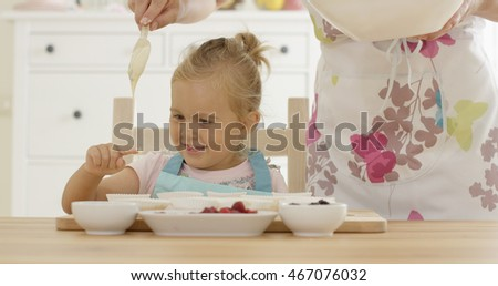 Laughing girl with muffin cups and parent in apron