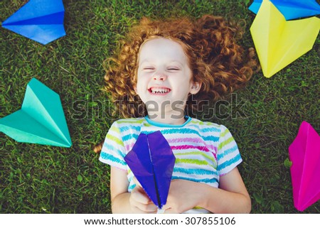 Laughing girl with paper airplane in her hand on green lawn. Happy childhood concept. - stock photo