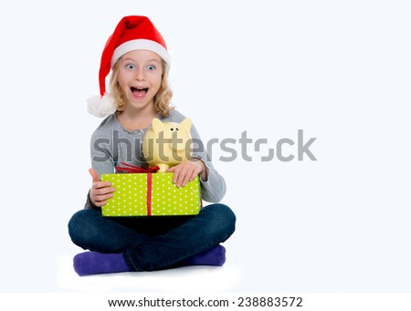laughing girl with Santa- cap gift and piggy bank - stock photo