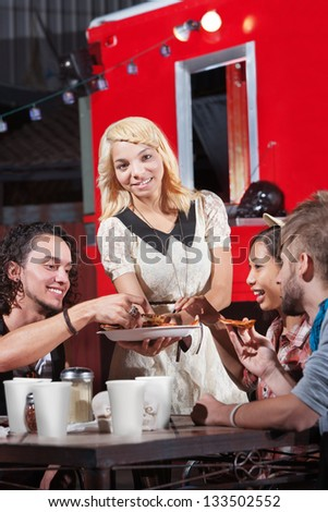 Laughing group of friends eating out at pizza restaurant - stock photo