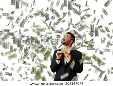 laughing happy man standing under dollar's rain, holding money and looking up - stock photo