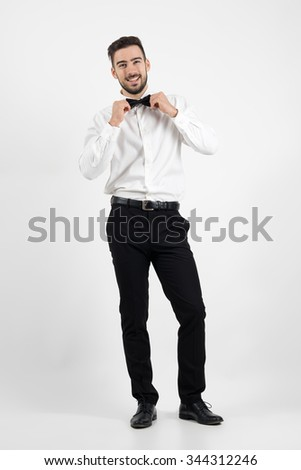 Laughing happy young bearded elegant man adjusting bow tie looking at camera. Full body length portrait over gray studio background. - stock photo