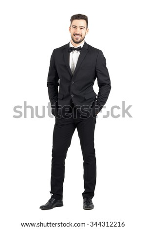 Laughing happy young man in tuxedo with bow tie looking at camera. Full body length portrait isolated over white studio background. - stock photo