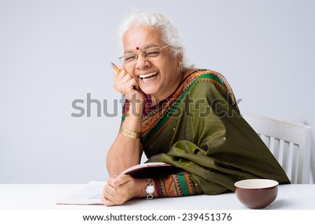 Laughing Indian woman with a book - stock photo