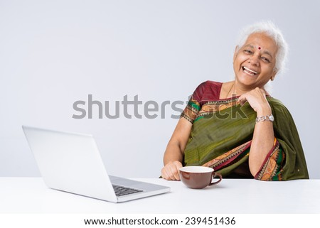 Laughing Indian woman with laptop sitting at the table - stock photo